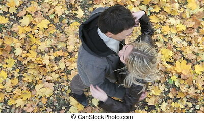 Young people viewed from above hugging affectionately in the autumn park