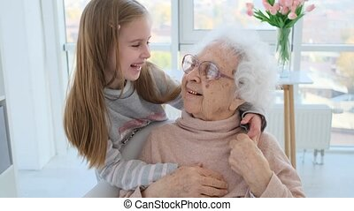 Tender hugs of granddaughter and grandmother at home