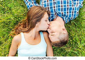 Tender kissing. Top view of a young couple in love lying together on the grass and kissing