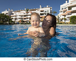 tender mom and baby smiling embraced in swimming pool