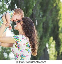 Tender mom tossing her baby child