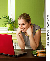 tender pregnant female with laptop working at home