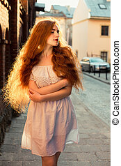 Tender red haired model with long curly hair wearing white dress posing in evening sunlight