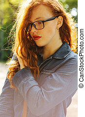 Tender red haired young woman in jeans shirt and glasses posing at the street