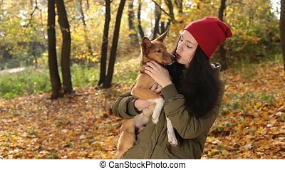 Tender scene of woman with dog in autumn park