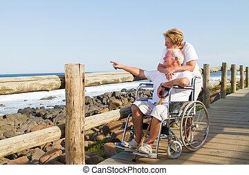 tender senior couple on beach - husband sitting in wheelchair