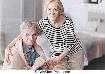 Tender senior wife taking care of her loving husband