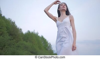 tender sensual spring fashion portrait of a beautiful happy young woman in white dress with long brown hair in the background of a blue sky