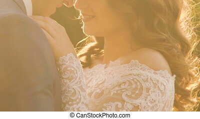 Tender wedding couple embracing and caressing in the golden sun rays outdoors