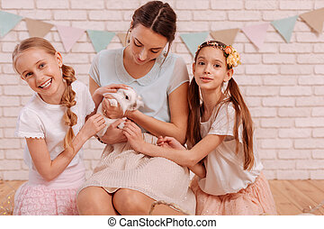 Tender young mommy holding rabbit in hands