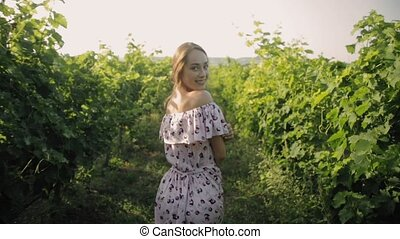 Tender young woman in the long dress walking along the rows of vineyard