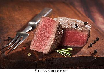 Tenderloin steak. - Juicy steak on dark wooden background....