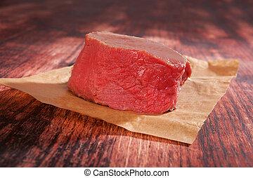 Raw tenderloin steak on baking paper on wooden background. Culinary steak eating.