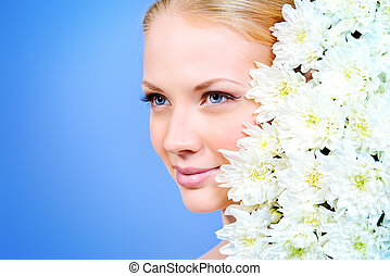 Close-up portrait of a beautiful blonde girl with white flowers of chrysanthemum. Healthcare. Make-up, cosmetics.