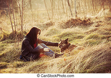 tenderness - girl with pariah dog sit in yellow grass warm...