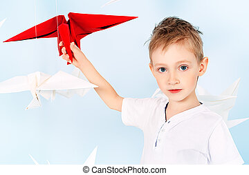 Happy little boy standing surrounded by paper birds. Dream world.