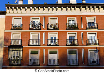 Red facade of traditional tenement house in Madrid, Spain.