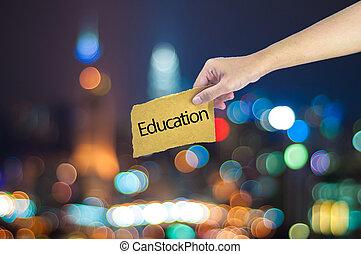 tenencia de la mano, un, educación, señal, hecho, en, azúcar, papel, con, luz de la ciudad, bokeh, como, plano de fondo
