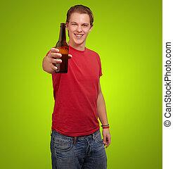 tenencia, encima, joven, cerveza, fondo verde, retrato, hombre