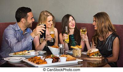 teniendo, amigos, feliz, el sentarse junto, cena