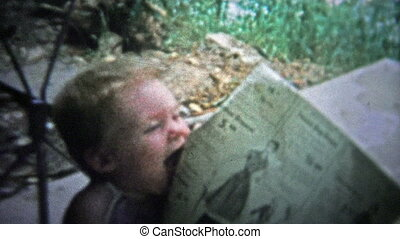 TENNESSEE, USA - 1954: Baby eating newspaper