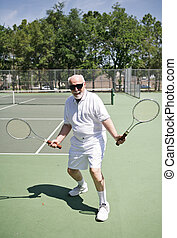 An active senior man on a tennis court with two rackets looking for someone to play.
