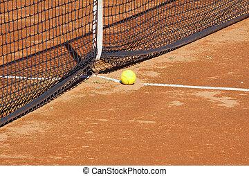 Tennis ball - A yellow tennis ball near the net on a clay...