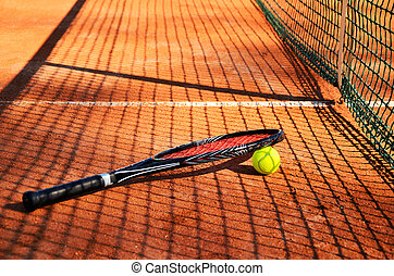 tennis ball and racket are near the net horizontal