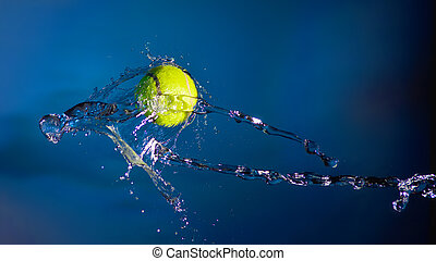Tennis ball and splashes of water on a blue background