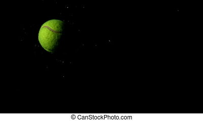 Tennis ball falling on black backg
