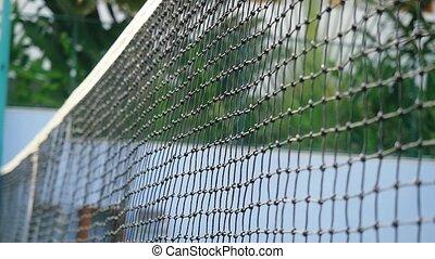 Tennis ball falling strikes against the grid on a tennis...