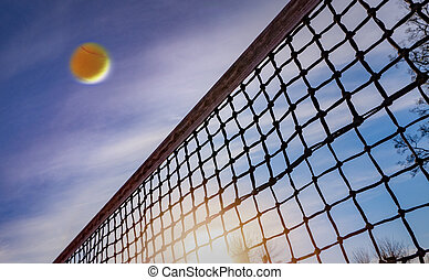 Tennis ball flying over middle net court on background blue sky