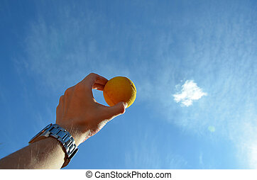 tennis ball in a man hand showing to the sky