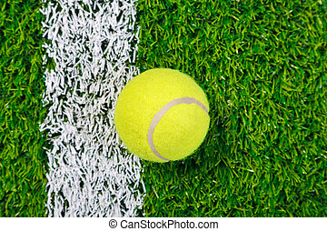 Tennis ball on grass from above.
