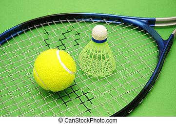 Tennis ball, shuttlecock and racket on green background