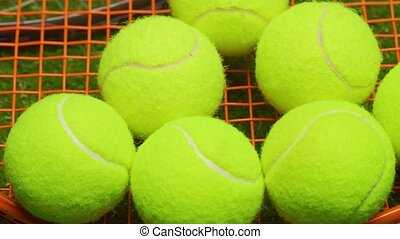 Tennis balls and racket on green grass background close up. High quality 4k footage