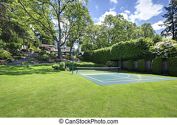 Tennis court with house on the hill and bright green grass.