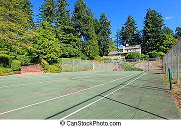 Tennis court wuth Large brown house exterior with summer garden. Northwest.
