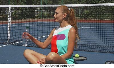 Tennis girl drinring water while relaxing on court