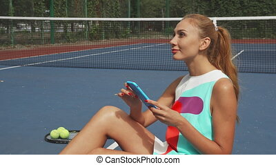 Tennis girl surfing the net while relaxing - Girl sitting on...