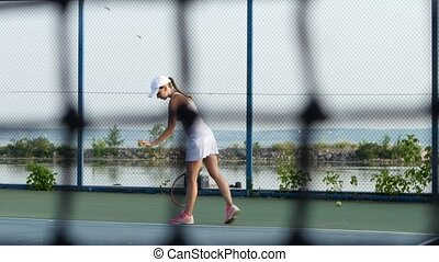 Tennis net and woman playing tennis in the background. Dolly shot