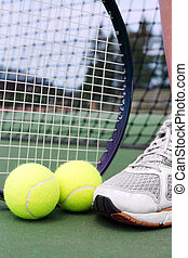Tennis shoe, racket and balls on a hard court in fron tof net.