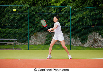 Tennis player about to hit ball