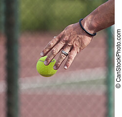 Tennis player bouncing  on court from hand