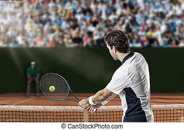 Tennis Player. - Tennis player returning a ball on a clay...