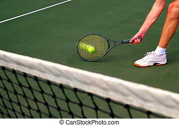 Tennis player running and hitting the ball
