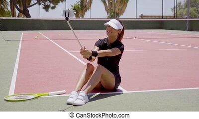 Tennis player taking a self portrait on court - Single...