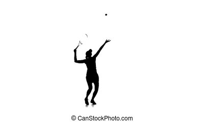 Tennis player throws the ball and smashes it. Silhouette. Slow motion