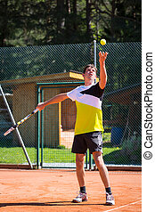 tennis player throws up ball to serve