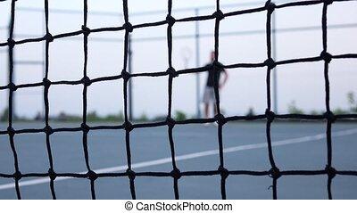Tennis player volleys using forehand technique. Tennis net...